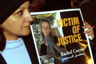 Palestinian woman holds photo of Rachel Corrie